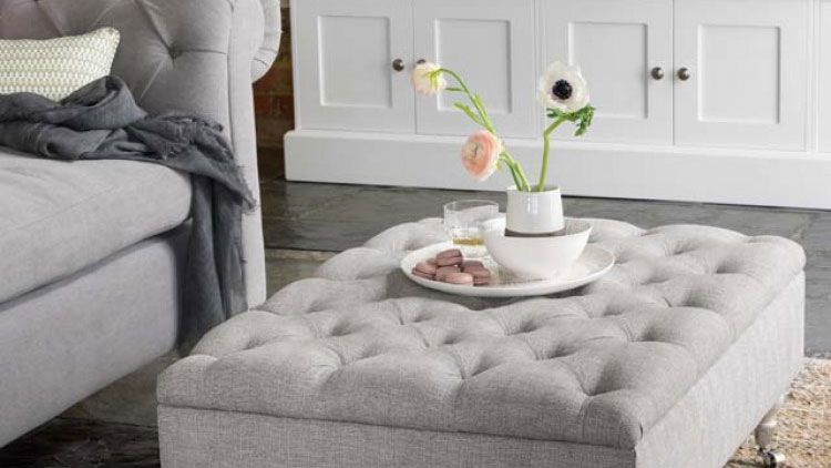 living room with grey ottoman style footstool by the dormy house