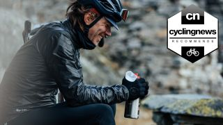 Cyclist in winter kit holding one of the best water bottles for cycling