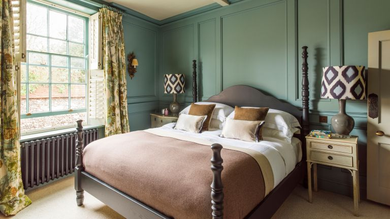 Luxury bedroom ideas in a green room with four poster bed and patterned fabrics.
