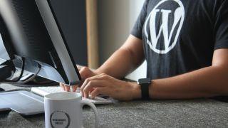 man in WordPress shirt working on computer