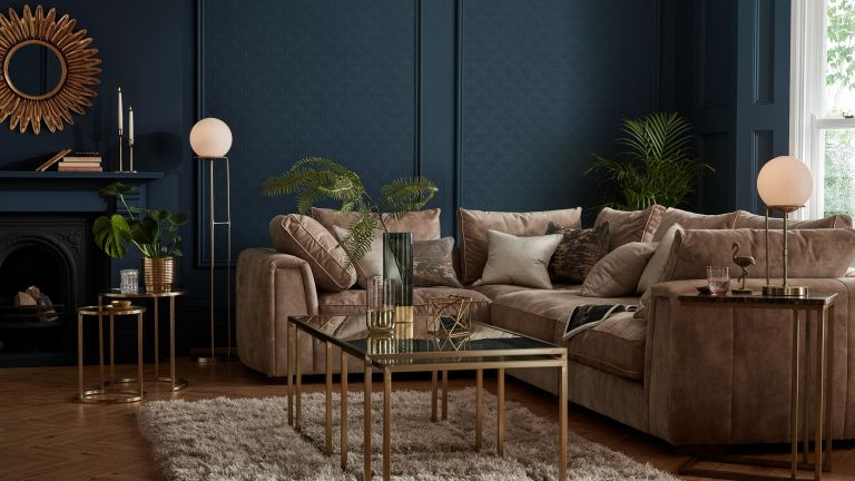 Navy living room corner idea by Sofology with statement gold round mirror, palm plants, fireplace and Art Deco inspired furniture