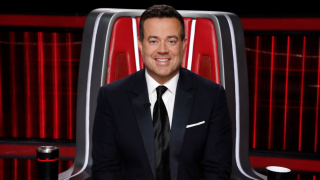 The Voice host Carson Daly sits in a coach's chair.