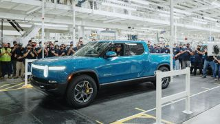 Electric truck rolling off a production line in a factory surrounded by workers