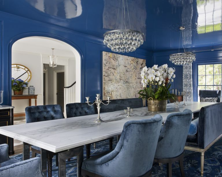 A dining room with blue gloss walls and ceiling and blue velvet chairs
