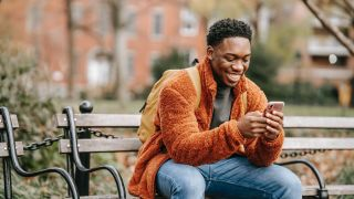 best Huawei phone: Smiling man using his phone on a park bench