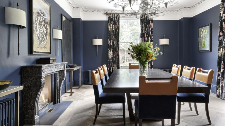 Dining room color ideas with navy walls, white ceilings, marble fireplace and orange dining chairs