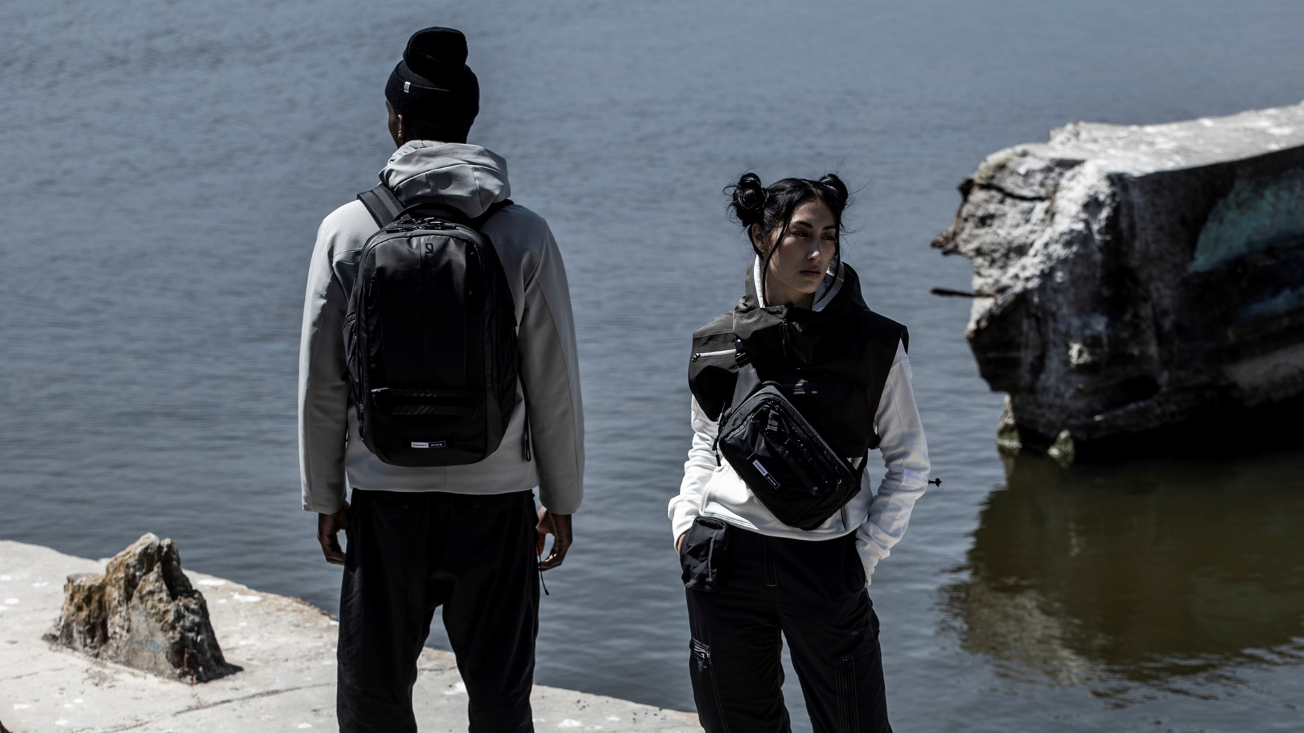 Two models. Female facing front with cross body bag and male model facing out to the ocean with back back.