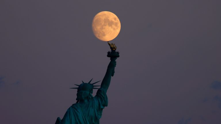 A 95 percent waxing crescent moon rises behind the Statue of Liberty in New York City on September 18, 2021 as seen from Jersey City, New Jersey.