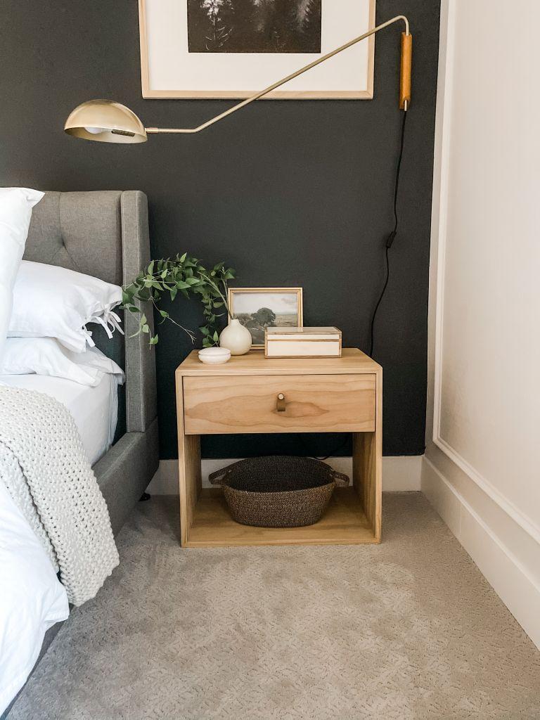 DIY wood nightstand against a dark wall