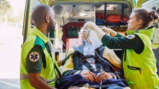 Male and female paramedics treat a man outside an ambulance