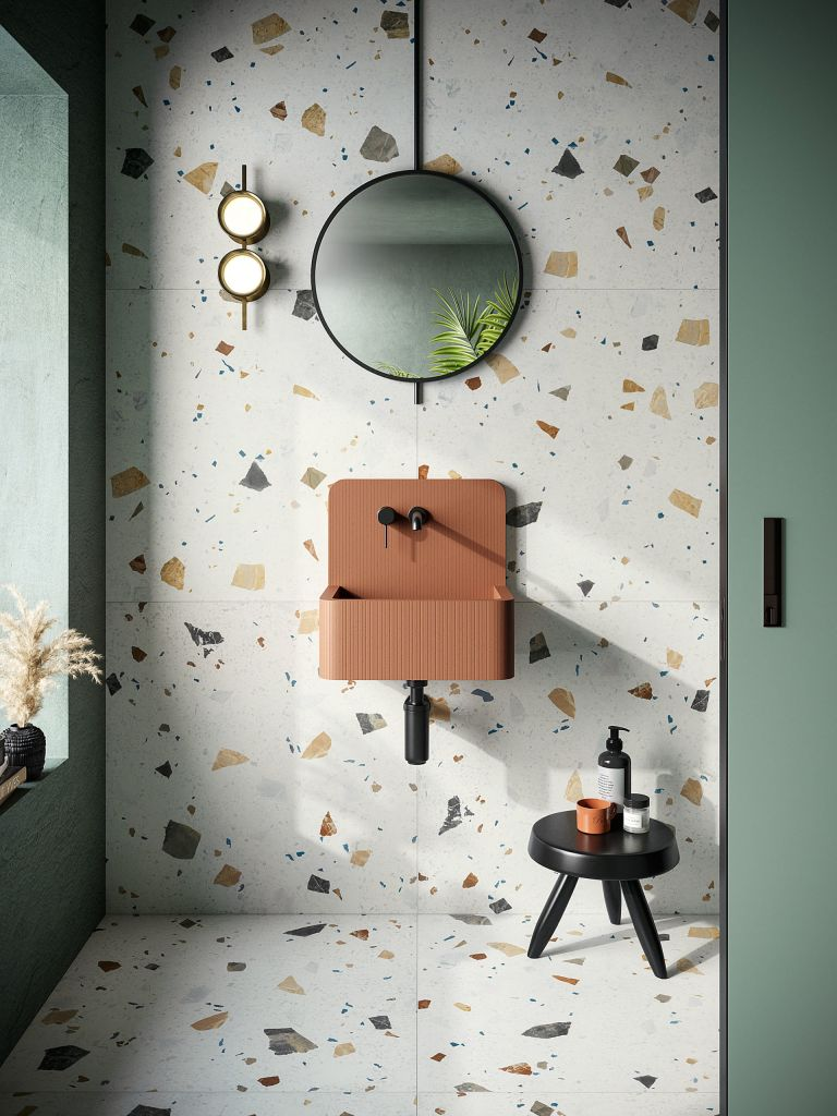 An example of tile trends 2021, showing terrazzo bathroom tiles behind a brown sink and black mirror.