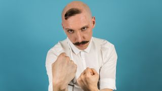 A press shot of Jamie Lenman raising his fists to the screen