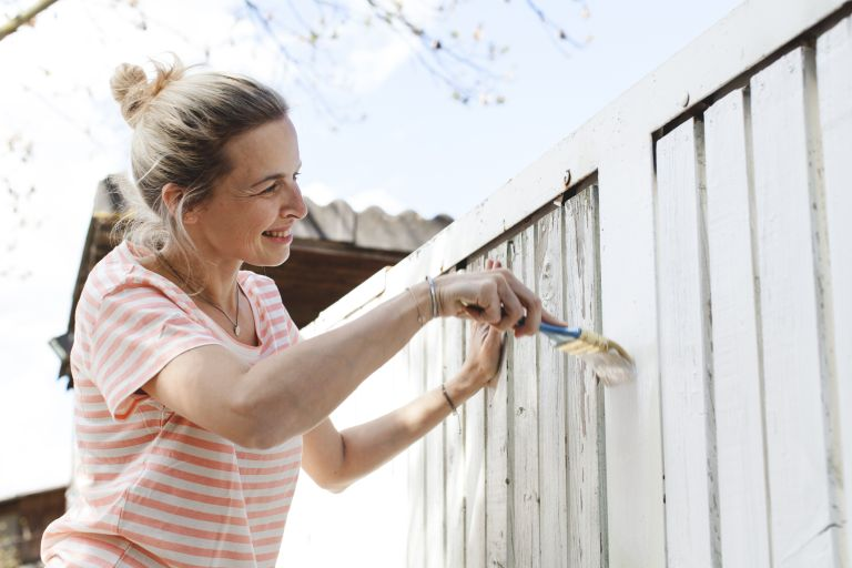 woman painting a fence