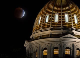 A perigee full moon, or supermoon, is seen during a total lunar eclipse behind The Colorado State Capitol building on September 27, 2015, in Denver, Colorado.