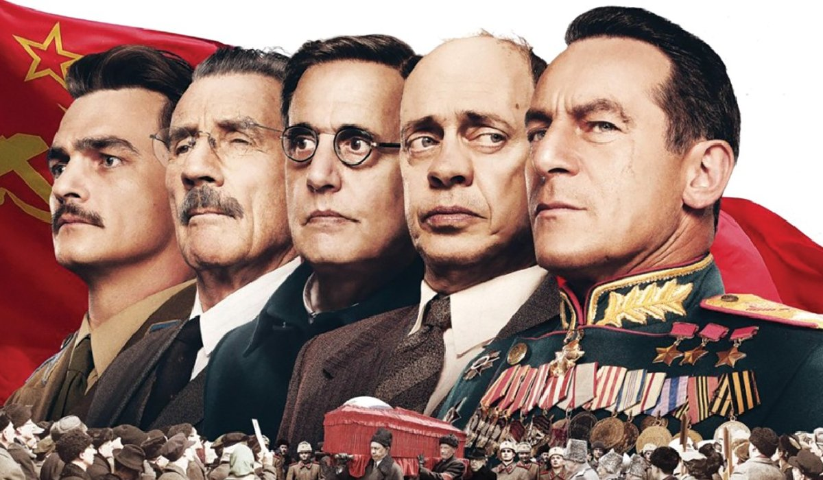 The Death of Stalin cast lines up in front of the Soviet flag