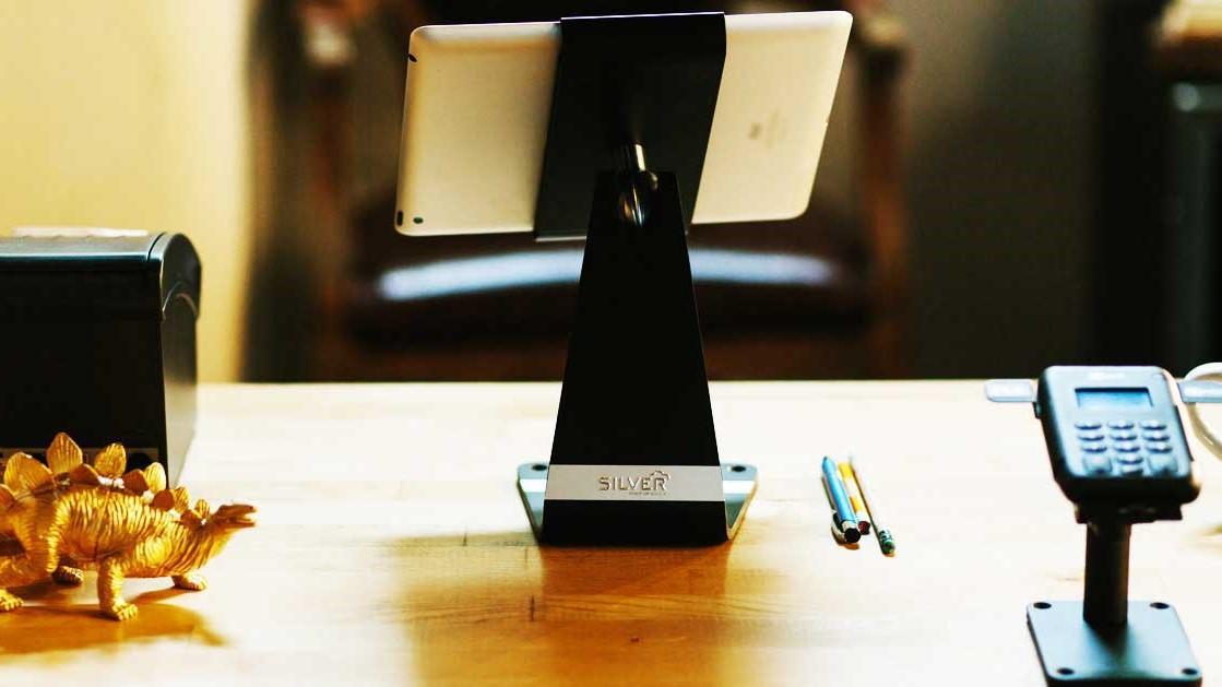 An iPad running the NCR Silver app with a receipt printer and an EMV Reader and Stand (Image Credit: NCR Silver)