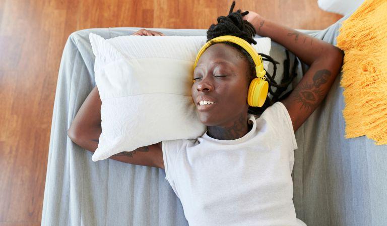 Woman asleep listening to ASMR through headphones