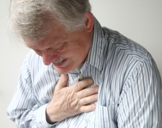 A man grips his chest in pain