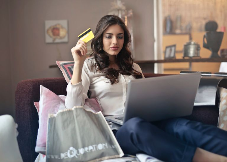 Laptop deals: Woman shopping online while holding credit card. Free stock photo from Unsplash