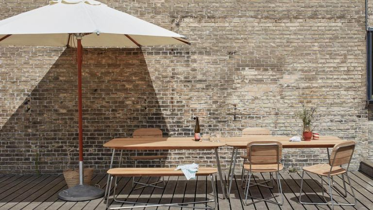 A large garden parasol over an outdoor dining table on a decked terrace