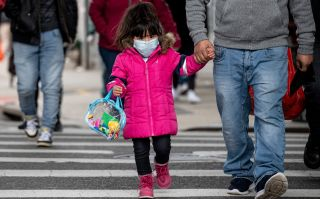 A girl walks down a street in the Corona neighborhood of Queens on April 14, 2020, in New York City.