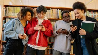 Four young people using phones to access the best video editing apps