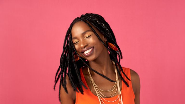 Smiling woman with box braids on a pink backdrop
