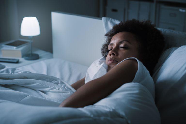 How much sleep do I need? Woman sleeping in darkened room