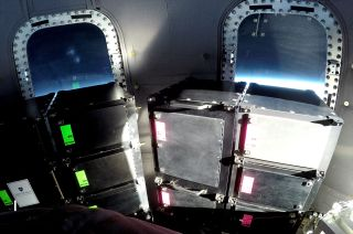 The blue haze of Earth's horizon glows through the windows behind payload racks aboard a Blue Origin New Shepard capsule in space. An auction benefiting SPACE on Ryder Farm is offering to fly an item of the winner's choice on a New Shepard flight.