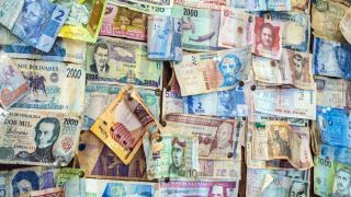 Different bank notes from difference countries pinned to a wall