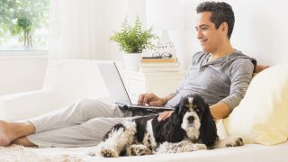 How do mattress warranties work: A man lies on his bed with his dog while reading about his mattress warrnty