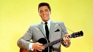 A photograph of Elvis Presley smiling and holding a guitar
