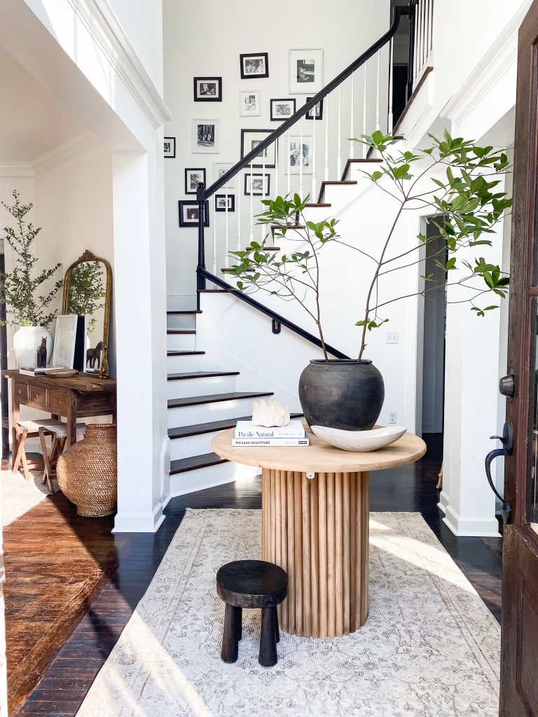 Modern entryway with gallery wall running up the stairs and small round console table at ground floor level