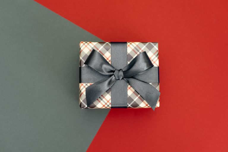 Tartan wrapped gift with grey bow on a red and grey background