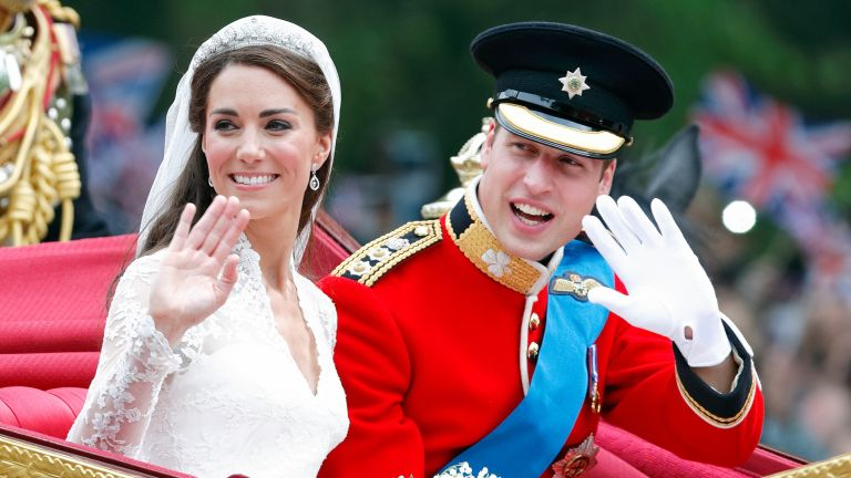 Prince William and Kate Middleton travel down The Mall, on route to Buckingham Palace, in the 1902 State Landau horse drawn carriage following their wedding ceremony at Westminster Abbey on April 29, 2011 in London, England