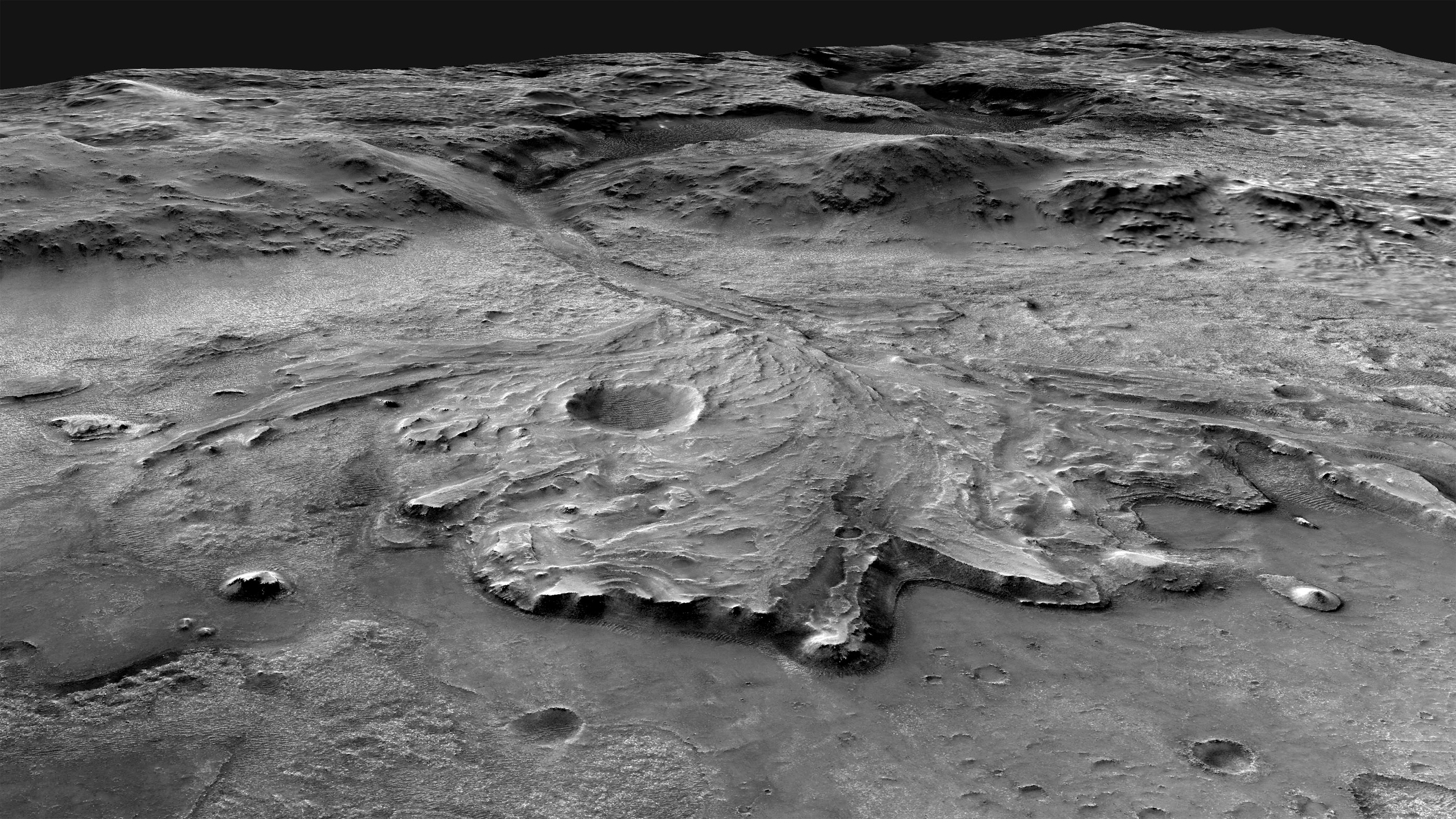 This oblique view looks to the west from above the Jezero crater floor, over the fan-shaped delta deposit, and into the valley that cuts through the crater rim.