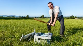 Man beating office printer with a bat in a field.