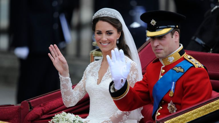Britain's Prince William and his wife Kate, Duchess of Cambridge, wave as they travel in the 1902 State Landau carriage along the Processional Route to Buckingham Palace