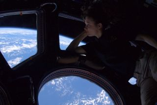 "Douglas H. Wheelock, ""Astro_Wheels"" on Twitter, shared this picture of Astronaut Tracy Caldwell Dyson looking down on Earth from the cupola of the International Space Station."