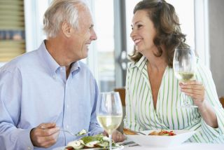 An older couple drinks wine together at a restaurant.