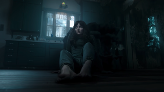 Madison sits on the floor in her kitchen looking terrified in a scene from Malignant.
