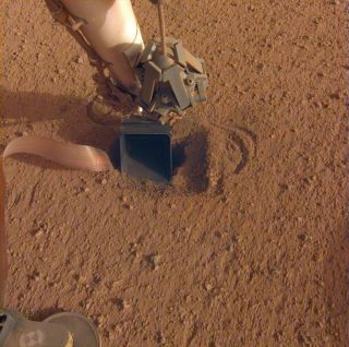 The burrowing heat probe aboard NASA's InSight Mars lander lies in a shallow pit beneath InSight's scoop, seen in this photo captured by the lander on June 20, 2020.