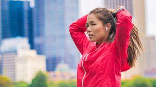 Woman preparing to start running, wearing true wireless headphones