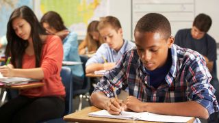 Teenage boy writes in his notebook in a classroom