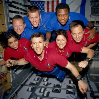 During the STS-107 mission, the crew appears to fly toward the camera in a group photo aboard the Space Shuttle Columbia. On the bottom row (L to R) are astronauts Kalpana Chawla, mission specialist; Rick D. Husband, mission commander; Laurel B. Clark, mi