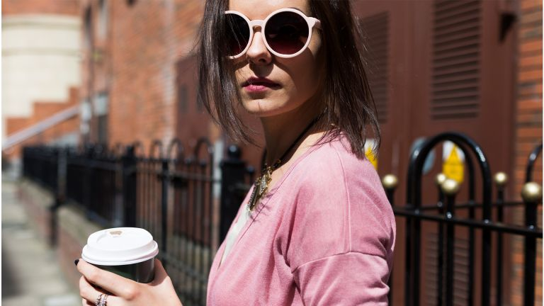 Fashionable young woman with coffee to go wearing pink sunglasses and cardigan - stock photo