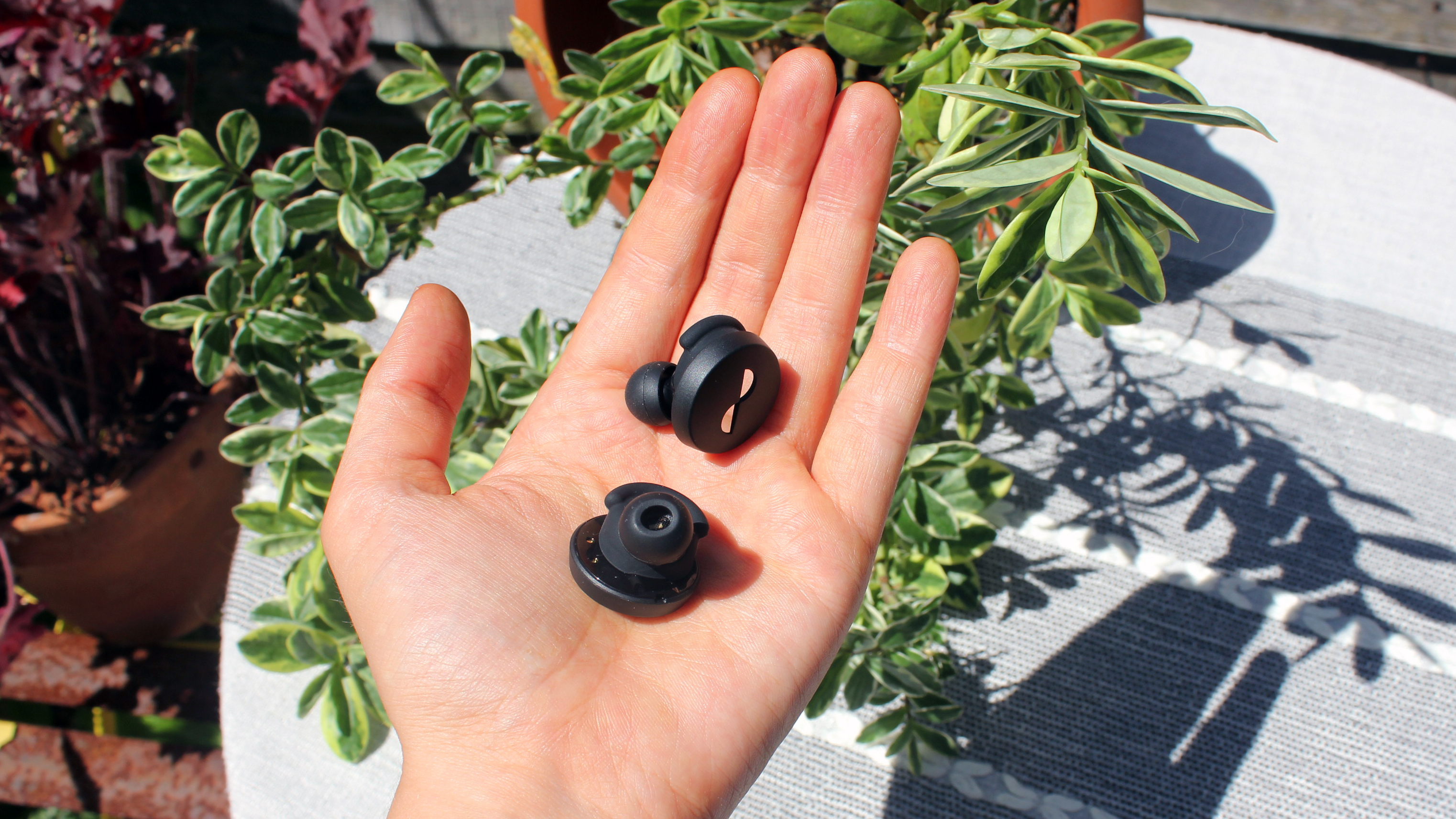 a open palm holding the the nuratrue earbuds