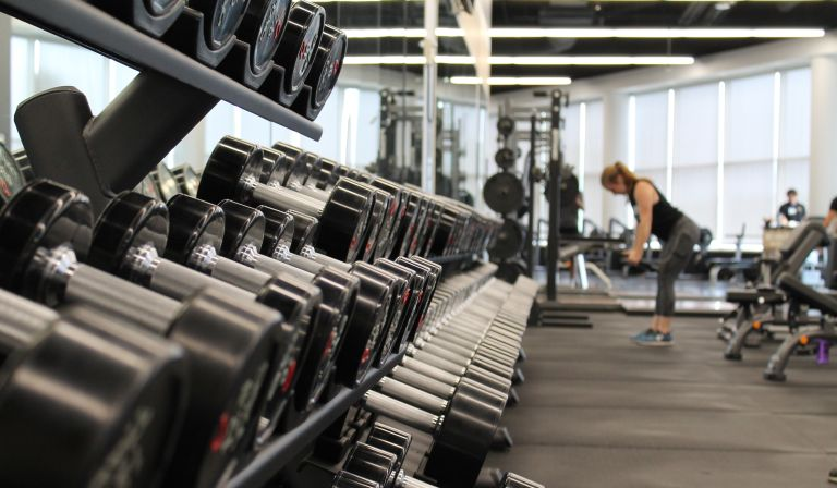 Rack of dumbbells woman in gym