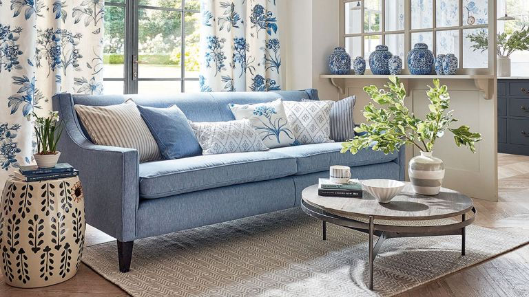 blue sofa in living space with coffee table and blue vases