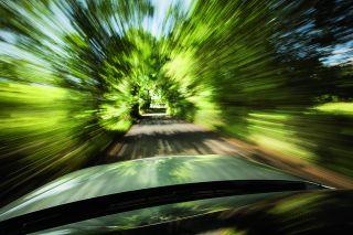 blurry trees alongside a road